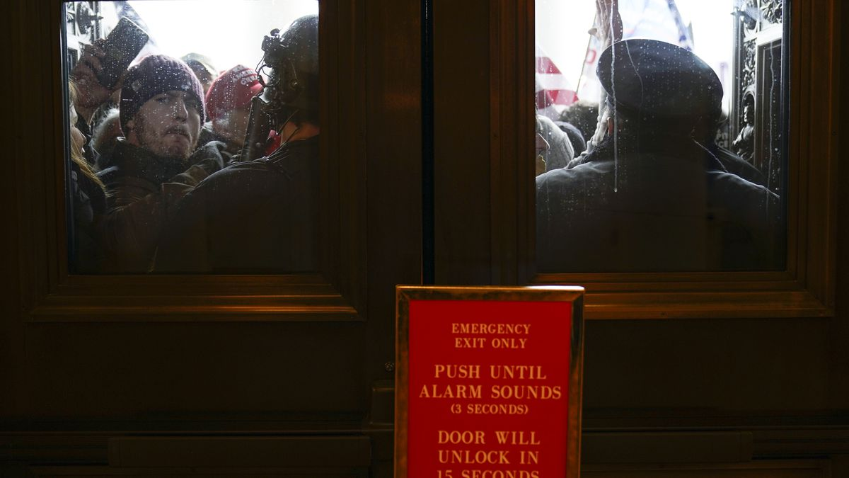 U.S. Capitol Police try to hold back protesters outside the east doors to the House side of the...