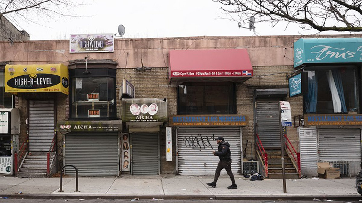 In this April 8, 2020, file photo, a pedestrian strolls past small businesses that are...
