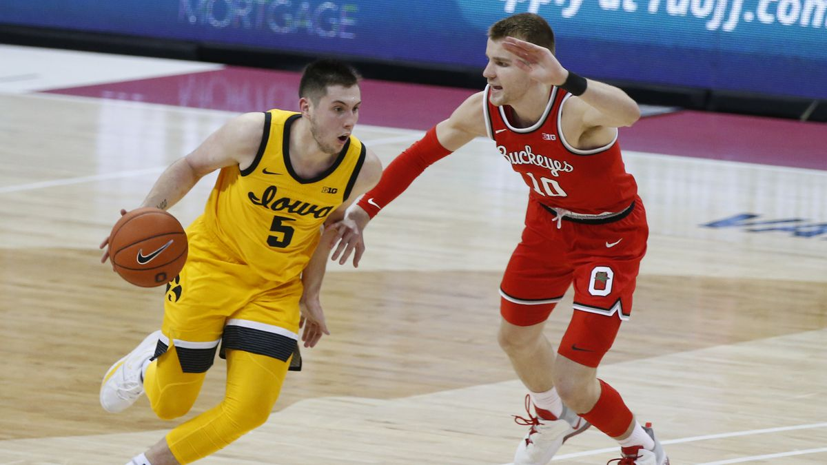 Iowa's C.J. Fredrick, left, dribbles past Ohio State's Justin Ahrens during the second half of...
