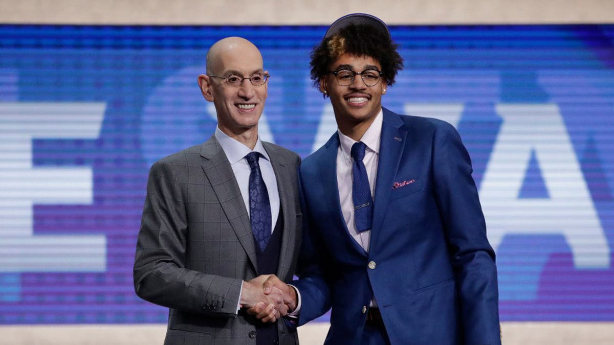 NBA Commissioner Adam Silver, left, poses for photographs with Michigan's Jordan Poole after the Golden State Warriors selected him as the 28th pick overall in the NBA basketball draft Thursday, June 20, 2019, in New York. (AP Photo/Julio Cortez)