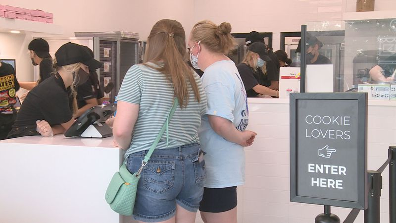 Customers pick out the cookies they want at Crumbl Cookies.