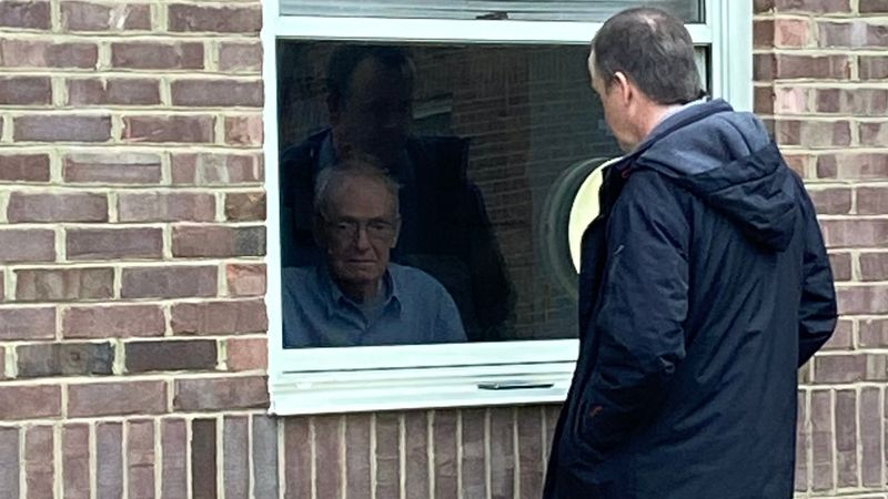 Bruce Edelen visits his father, a WWII veteran, through a window due to visitation restrictions...