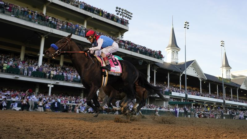 John Velazquez rides Medina Spirit across the finish line to win the 147th running of the...