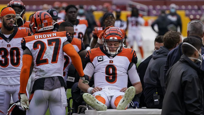 Cincinnati Bengals quarterback Joe Burrow (9) is consoled by teammates as he is carted off the...