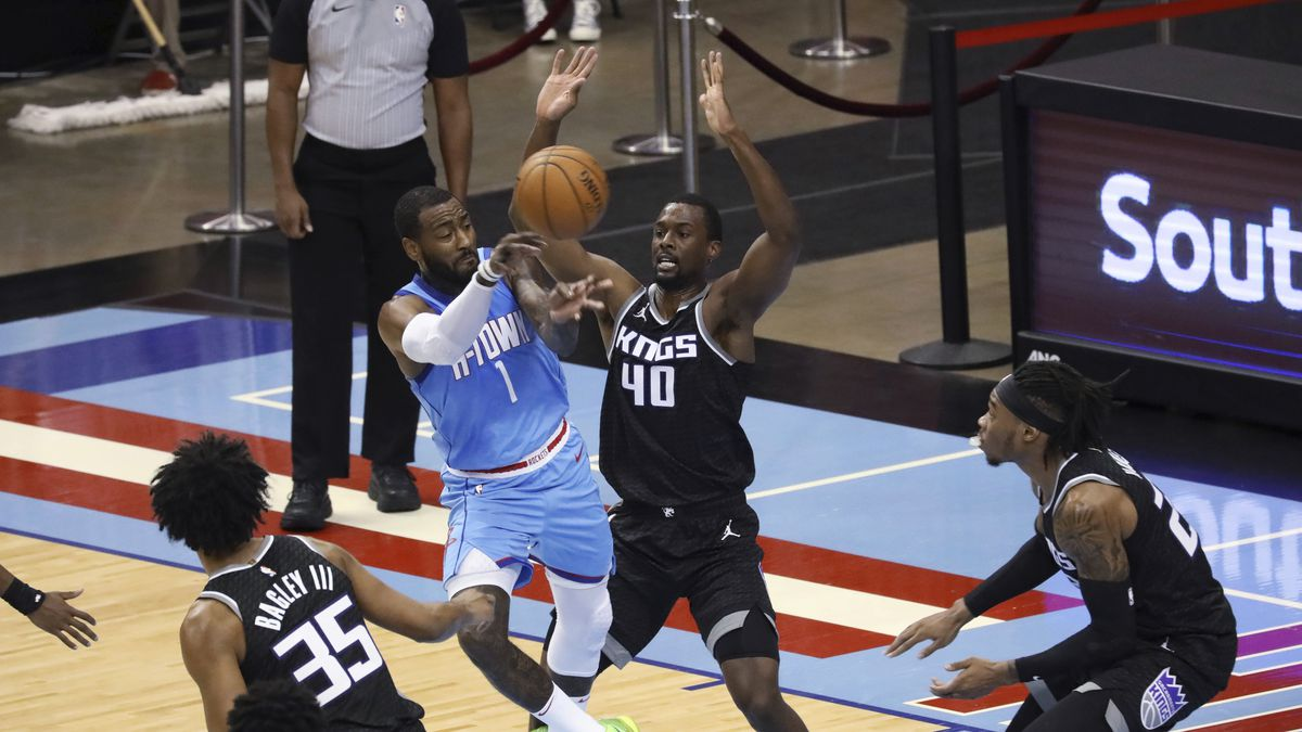 Houston Rockets guard John Wall passes the ball around Sacramento Kings' Harrison Barnes during...