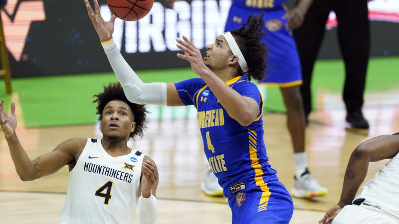 Morehead State's Johni Broome, right, reaches a rebound before West Virginia's Miles McBride,...