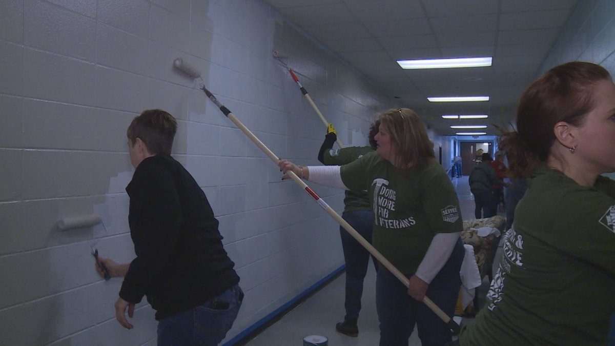 Volunteers add a new coat of paint to the wall, as they prepare the former school to become a...