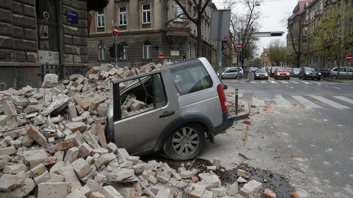 A car is crushed by falling debris after an earthquake in Zagreb, Croatia, Sunday, March 22, 2020. A strong earthquake shook Croatia and its capital on Sunday, causing widespread damage and panic. (AP Photo/Darko Bandic)