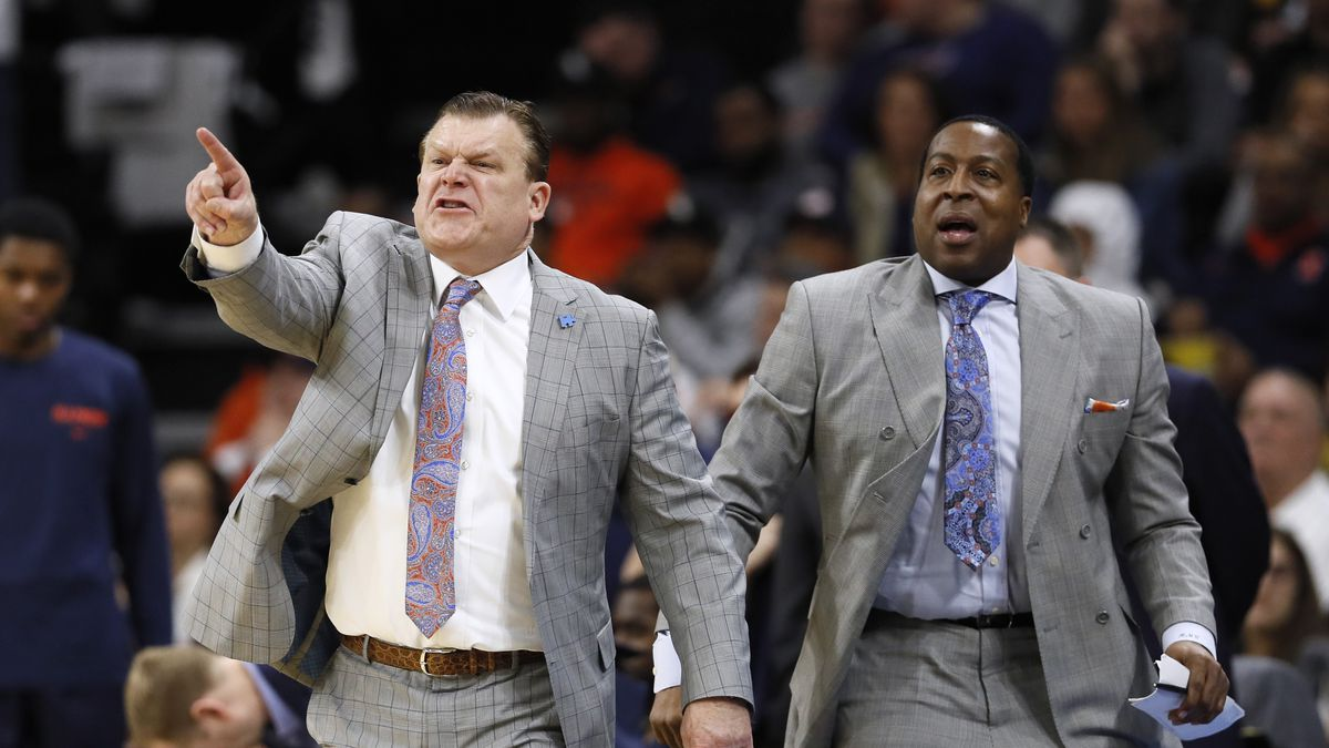 Illinois head coach Brad Underwood, left, and assistant coach Ron Coleman react on the bench...