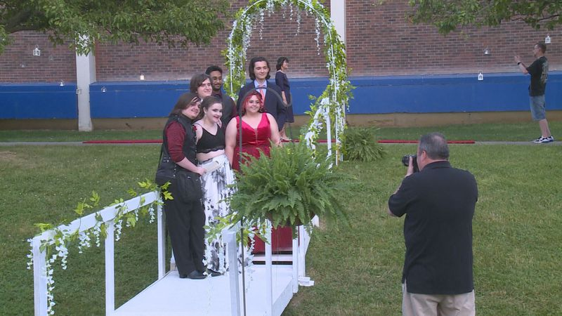 Seniors get their pictures taken as they head into prom.