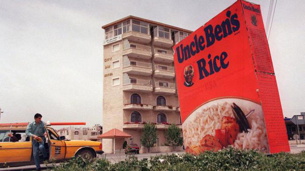 A Palestinian man gets out of taxi next to a huge metal box advertising Uncle Ben's Rice, in...