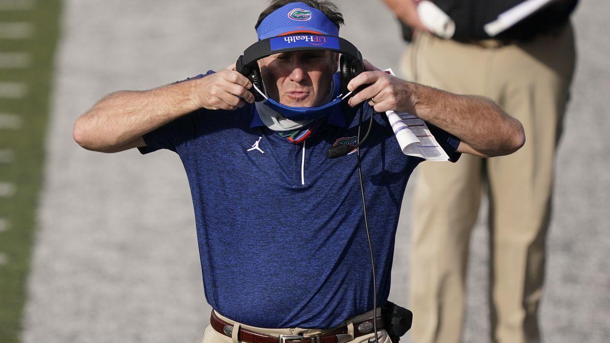 Florida head coach Dan Mullen puts on his earphones in the second half of an NCAA college...