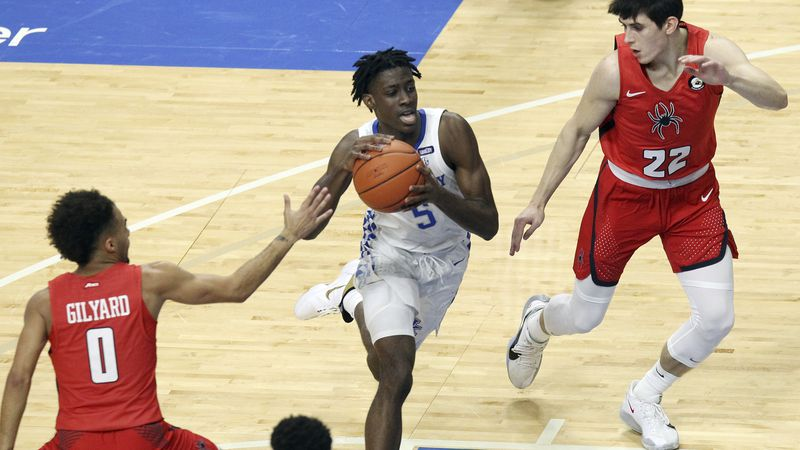 Kentucky's Terrence Clarke, center, drives between Richmond's Jacob Gilyard (0) and Andre...