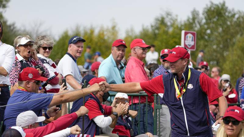 Team USA captain Steve Stricker greets fans on the second hole during a Ryder Cup singles match...