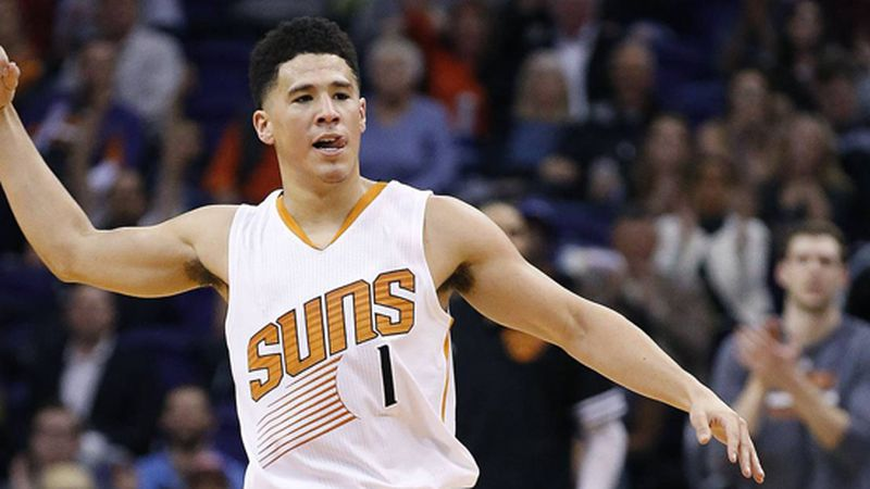 Phoenix Suns' Devin Booker celebrates a 3 point shot against the Charlotte Hornets during the...
