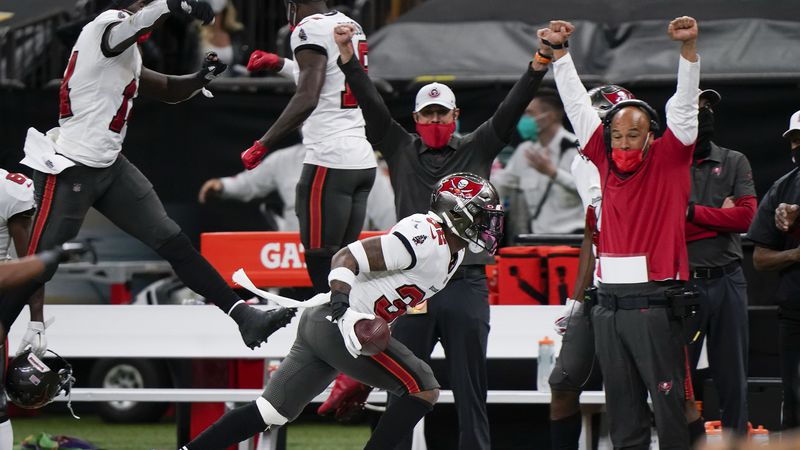 Tampa Bay Buccaneers players and coaches celebrate on the sideline as safety Mike Edwards (32)...