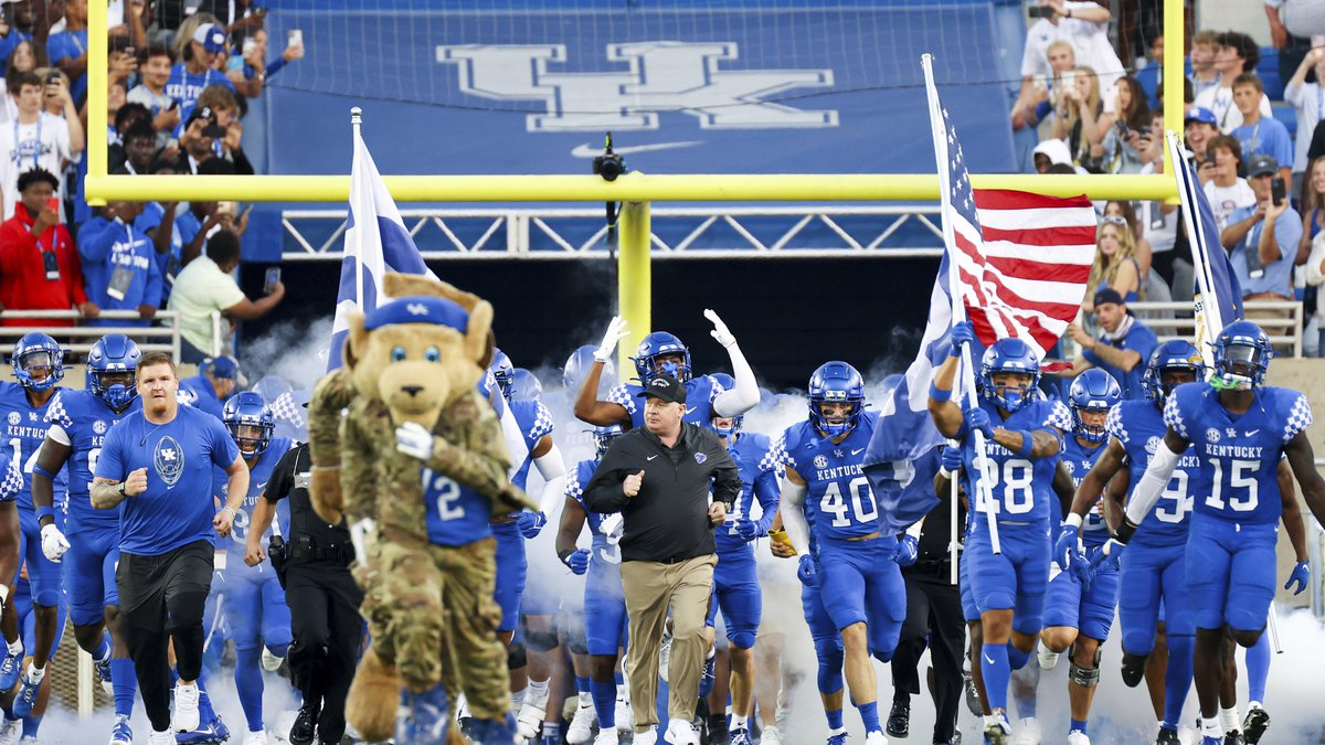 Kentucky head coach Mark Stoops (center) runs out with his team before an NCAA college football...