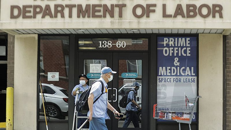 Pedestrians pass an office location for the New York State Department of Labor Thursday, June...
