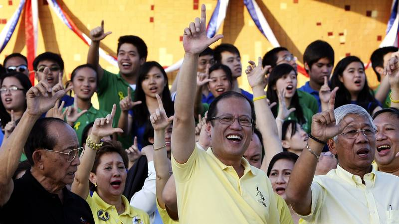 In this Feb. 25, 2011, file photo, Philippine President Benigno Aquino III, center, former...
