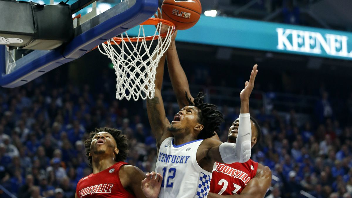 Kentucky's Keion Brooks Jr. (12) shoots between Louisville's Dwayne Sutton (24) and Steven Enoch during the first half of an NCAA college basketball game in Lexington, Ky., Saturday, Dec. 28, 2019. (AP Photo/James Crisp)