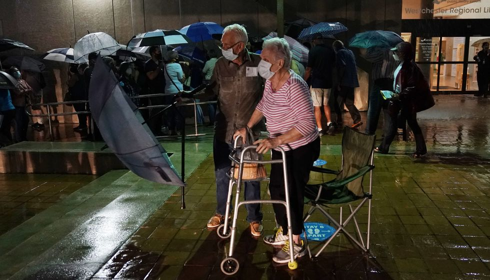 A couple stands in line as rain falls on voters waiting for the precinct to open, Monday, Oct....