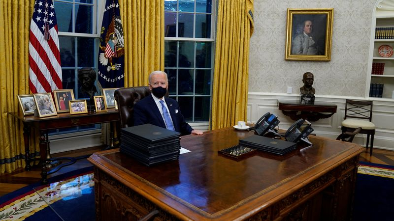 President Joe Biden signs his first executive orders in the Oval Office of the White House on...