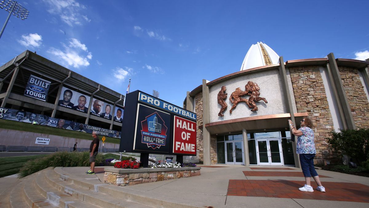 FILE - In this Aug. 7, 2015, file photo, a visitor to the Pro Football Hall of Fame pauses to take a photo of the sign in front in Canton, Ohio. The NFL has canceled the Hall of Fame game that traditionally opens the preseason and is delaying the 2020 induction ceremonies because of the coronavirus pandemic, two people with direct knowledge of the decision told The Associated Press on Thursday, June 25, 2020. The people spoke to the AP on condition of anonymity because the decision has not been publicly announced, though an announcement is expected later Thursday.