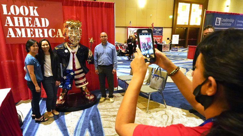 Conference attendees pose for a photo next to a statue of former President Donald Trump at the...
