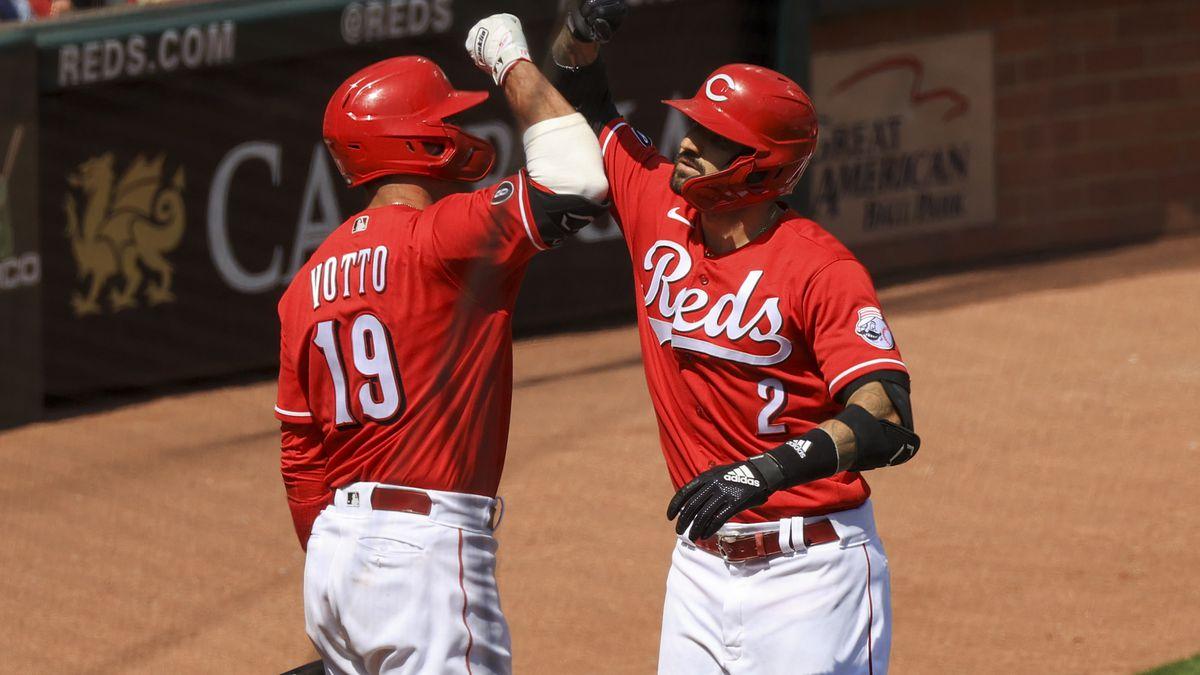 Cincinnati Reds' Joey Votto, left, celebrates the three-run home run by Nick Castellanos,...