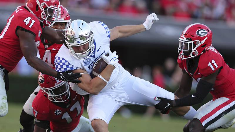 Kentucky tight end Justin Rigg (83) is tacked by Georgia linebacker Channing Tindall (41),...