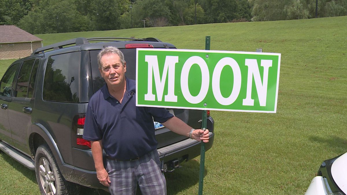 Langley Franklin holds up a portable sign for Moon, Kentucky, as he says the last two times...