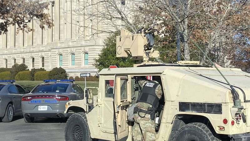 Police, along with military police and military humvees, state trooper cruisers and dozens of...