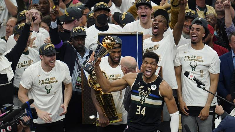 Milwaukee Bucks forward Giannis Antetokounmpo (34) holds up the MVP trophy after defeating the...