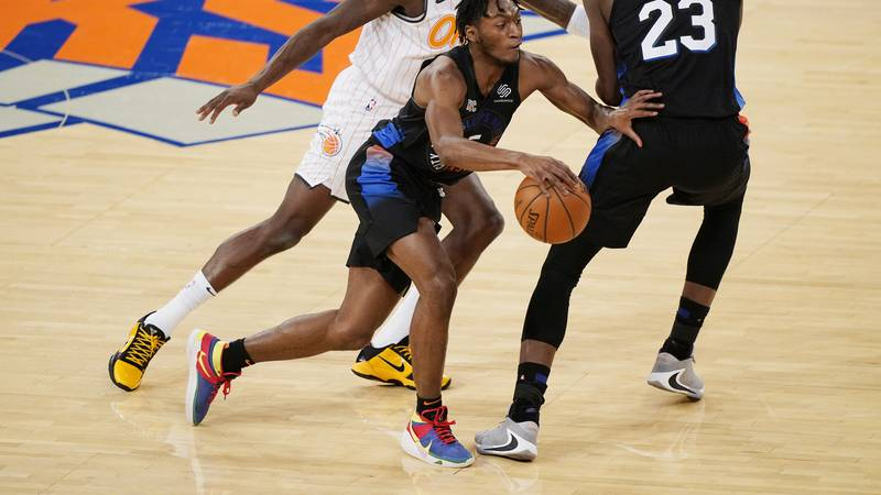 New York Knicks guard Immanuel Quickley (5) drives past Orlando Magic forward James Ennis III,...