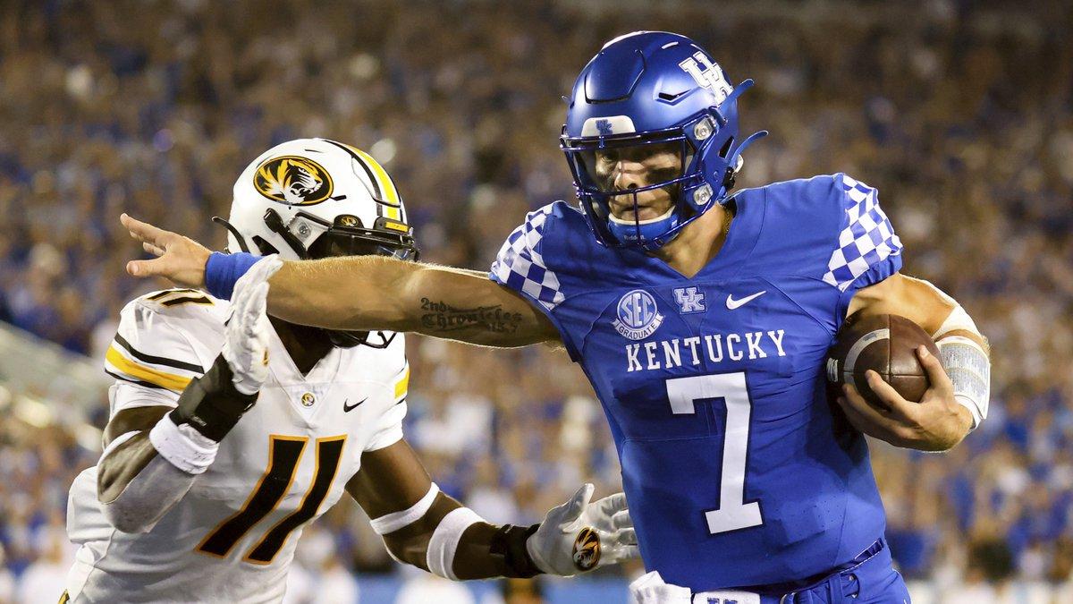 Kentucky quarterback Will Levis (7) stiff arms Missouri linebacker Devin Nicholson (11) on his...