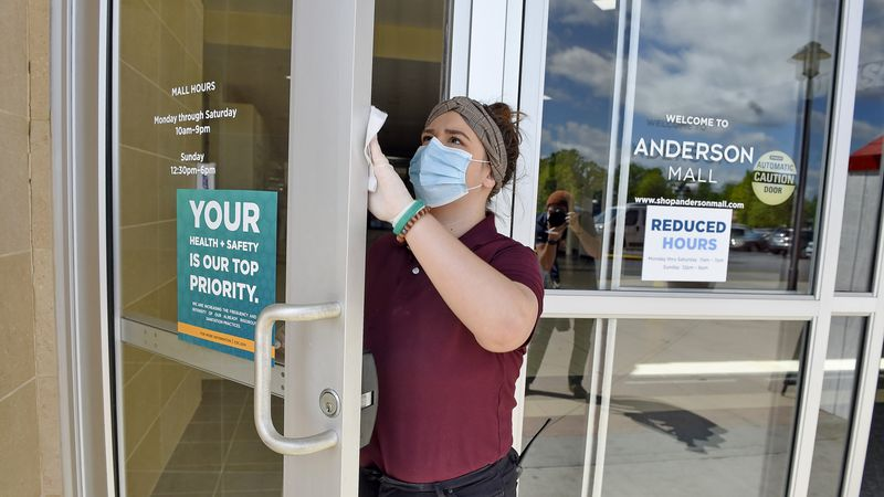 In this April 24, 2020 file photo, Kendall Ballew, an employee of the Anderson Mall, cleans the...