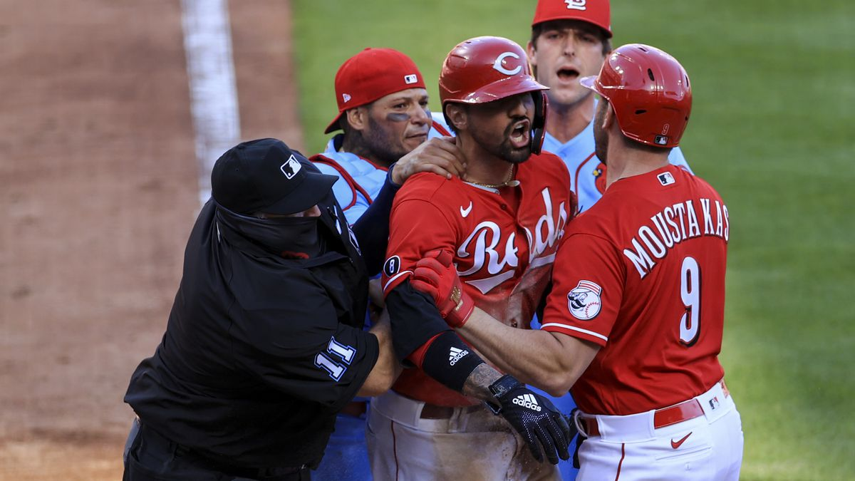MLB umpire Tony Randazzo, left, reacts as St. Louis Cardinals' Yadier Molina, middle left,...