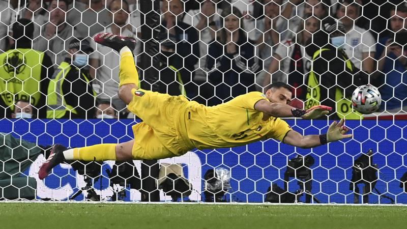 Italy's goalkeeper Gianluigi Donnarumma makes a save against England's Jadon Sancho during...