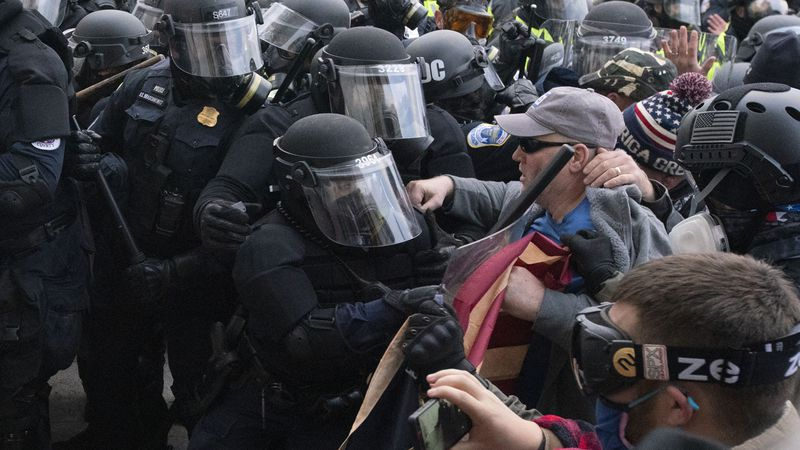Capitol police officers in riot gear push back demonstrators who try to break a door of the...