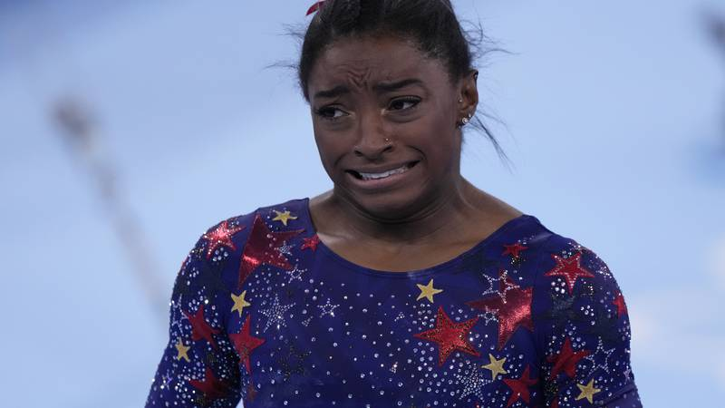 Simone Biles, of the United States, reacts after performing on the uneven bars during the...
