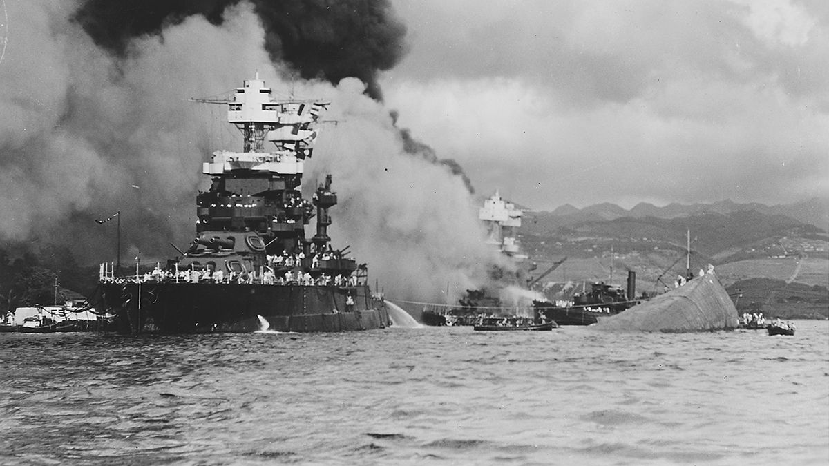 The capsized USS Oklahoma on the right is next to the USS Maryland after the Dec. 7, 1941...