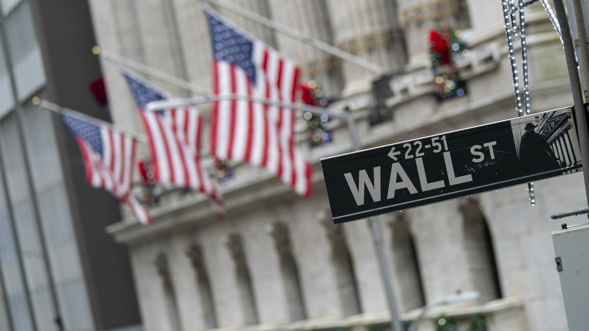 FILE - In this Friday, Jan. 3, 2020 file photo, the Wall St. street sign is framed by American...