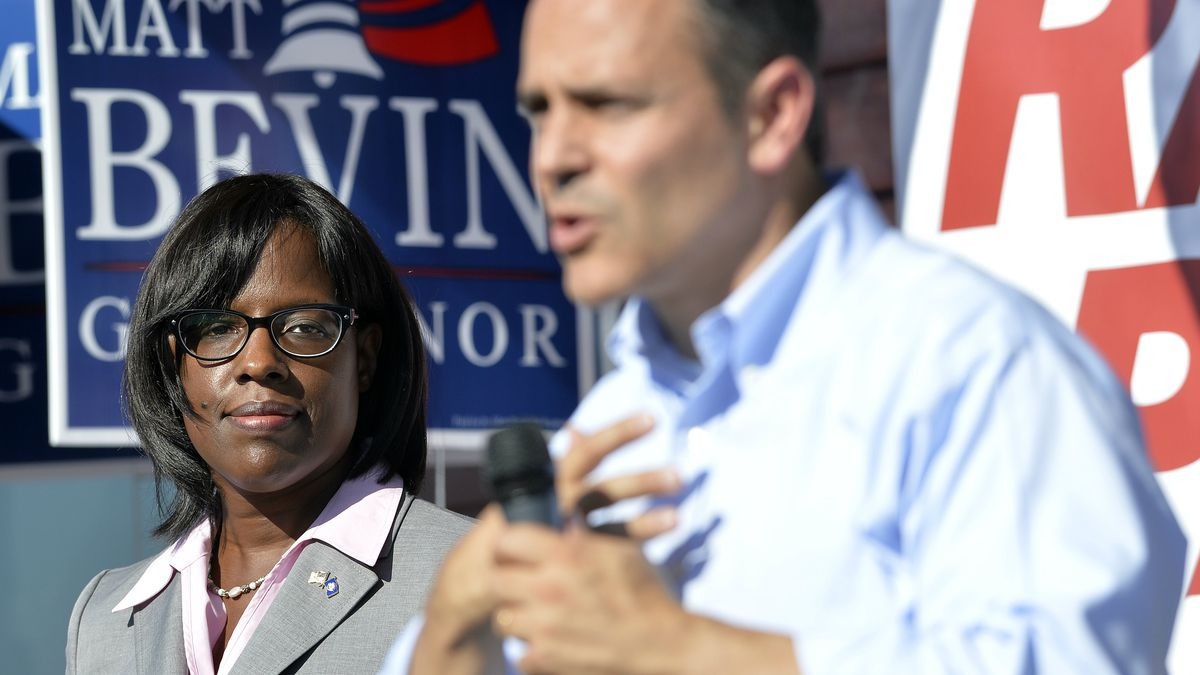 Kentucky Republican Lt. Gubernatorial candidate Jenean Hampton, left, looks on as her running mate, Gubernatorial candidate Matt Bevin, addresses their supporters from the steps of the Bevin campaign headquarters in Somerset Ky., Friday, Aug. 21, 2015. (AP Photo/Timothy D. Easley)