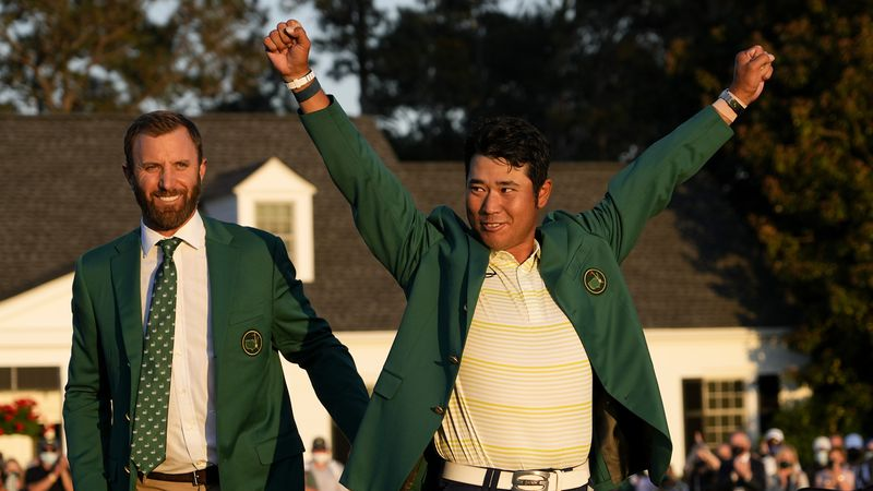 Hideki Matsuyama, of Japan, puts on the champion's green jacket after winning the Masters golf...