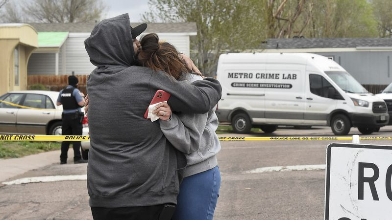 Freddy Marquez kisses the head of his wife, Nubia Marquez, near the scene where her mother and...