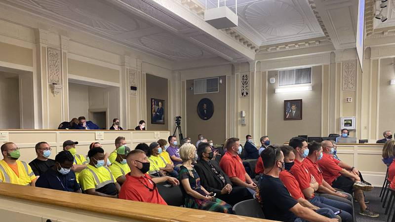 """Firefighters and city workers watched on as a resolution to allocate $15 million for """"hero pay""""..."""