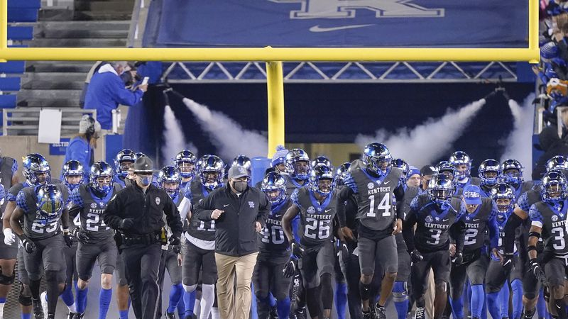 Kentucky players, led by head coach Mark Stoops run onto the field before an NCAA college...