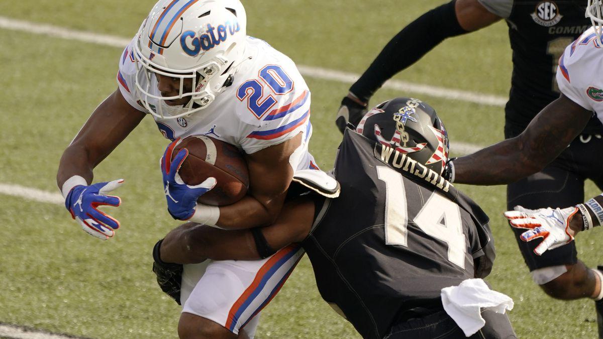 Florida running back Malik Davis (20) is hit by Vanderbilt safety Maxwell Worship (14) in the...