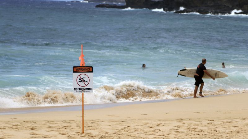 A surfer leaves the water in Honolulu, Saturday, July 25, 2020, as Hurricane Douglas...