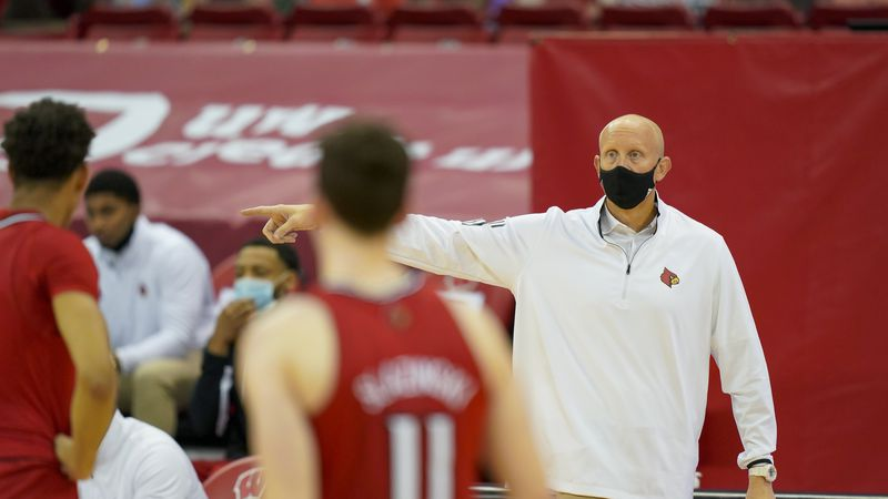 Louisville head coach Chris Mack talks to his team during the second half of an NCAA college...